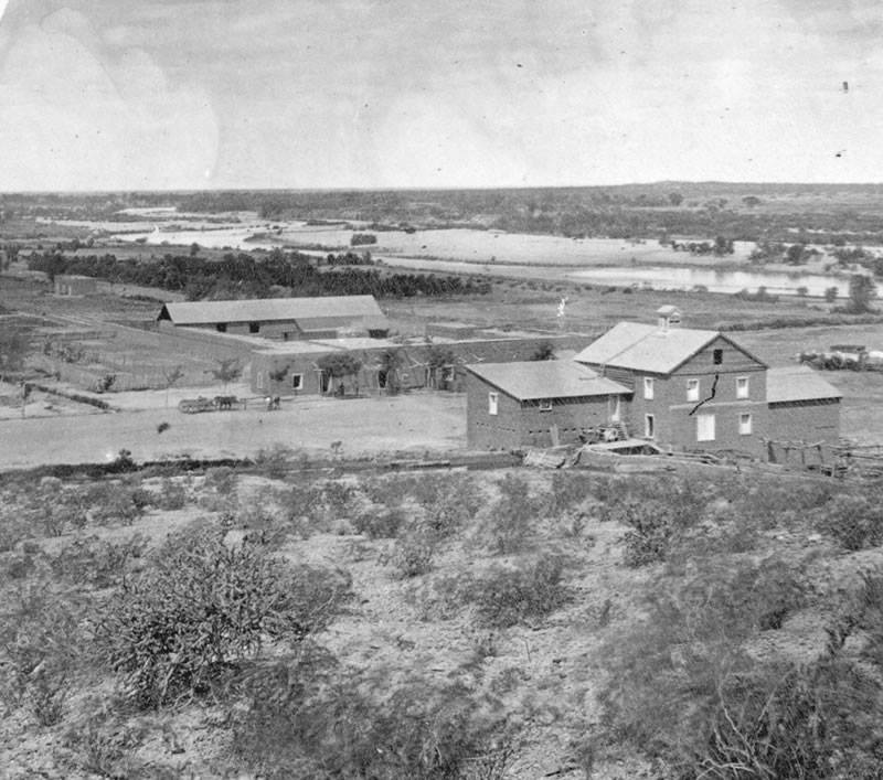 circa 1890 - Mill Ave near the Salt River, Hayden Mill in the foreground, the long building across from the Mill was built by Charles Trumbull Hayden in 1871, the oldest building in Tempe,  Monti's Casa Vieja Restaurant was located in this building from 1956-2014