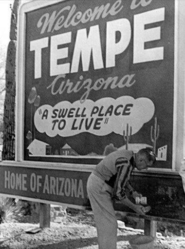 1953 - Vic Palmer of the Chamber of Commerce paints a Welcome sign at Tempe's Mill Avenue Bridge